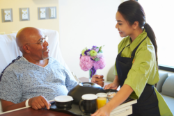 Caregiver giving meal to elder